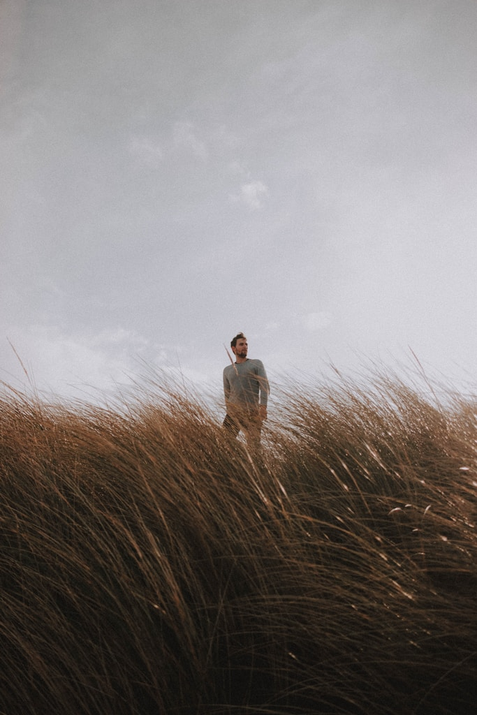 man in white dress shirt standing on brown grass field under white cloudy sky during daytime
