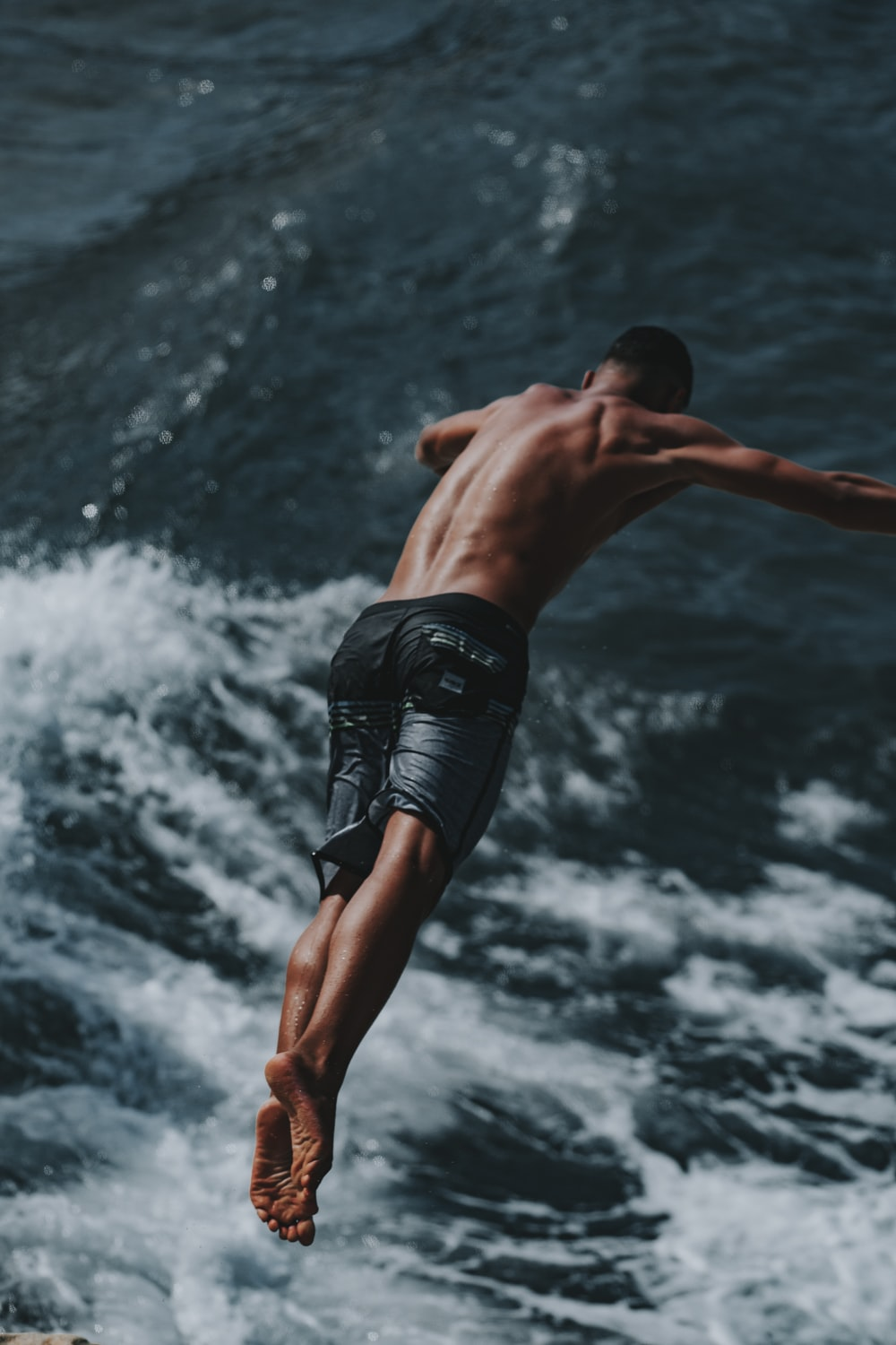 man in black shorts jumping on water