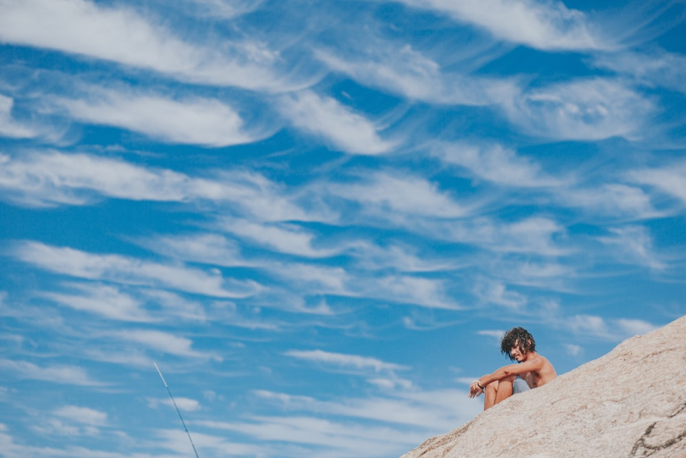 woman in black bikini sitting on rock under blue sky and white clouds during daytime