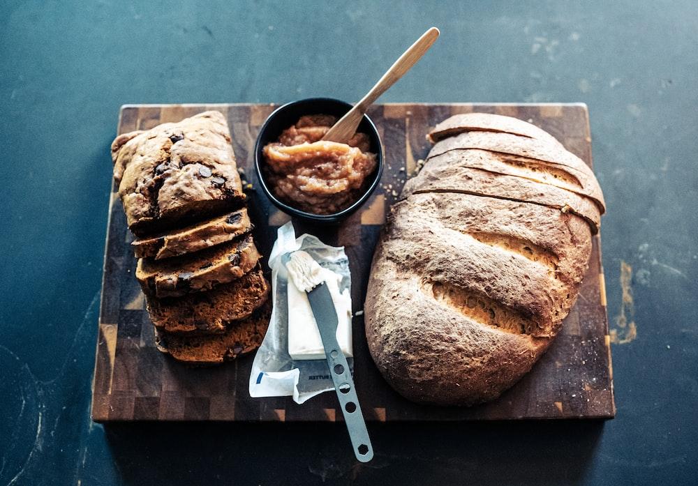 bread on black ceramic plate beside stainless steel knife