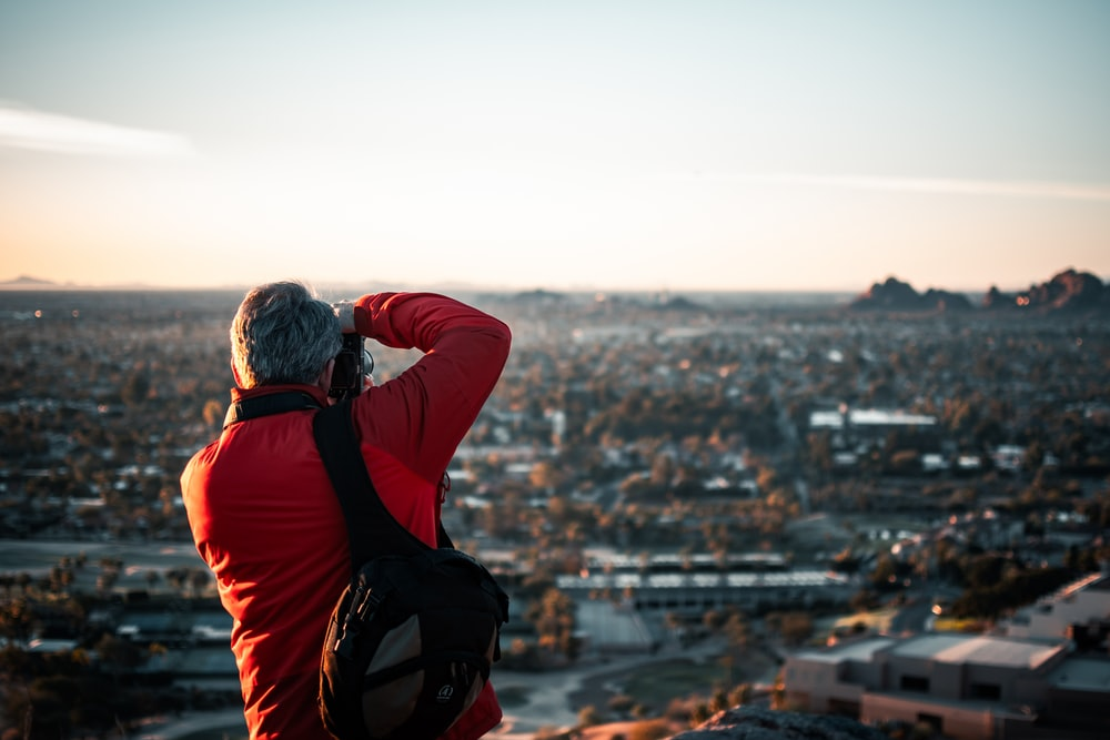 man in red and black jacket sitting on rock looking at city buildings during daytime