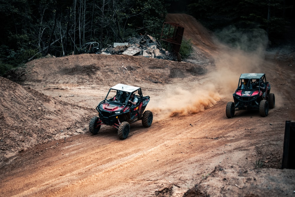 black and red atv on brown dirt road during daytime