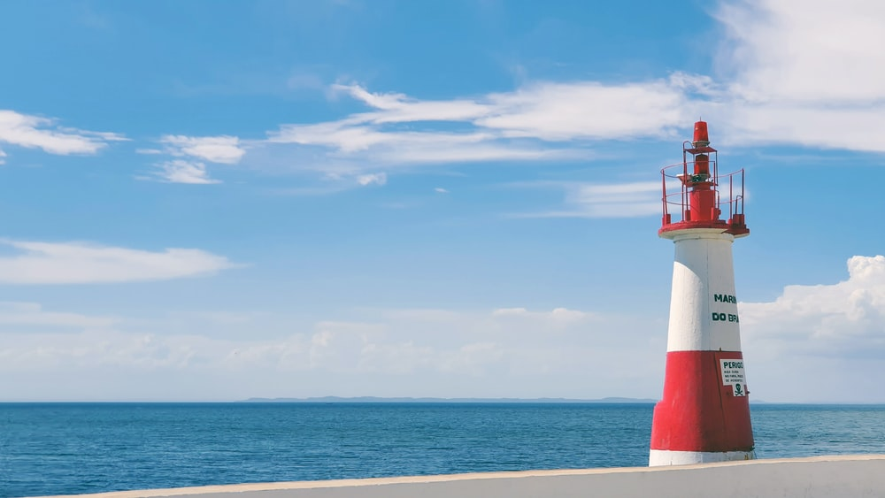 red and white lighthouse on beach during daytime