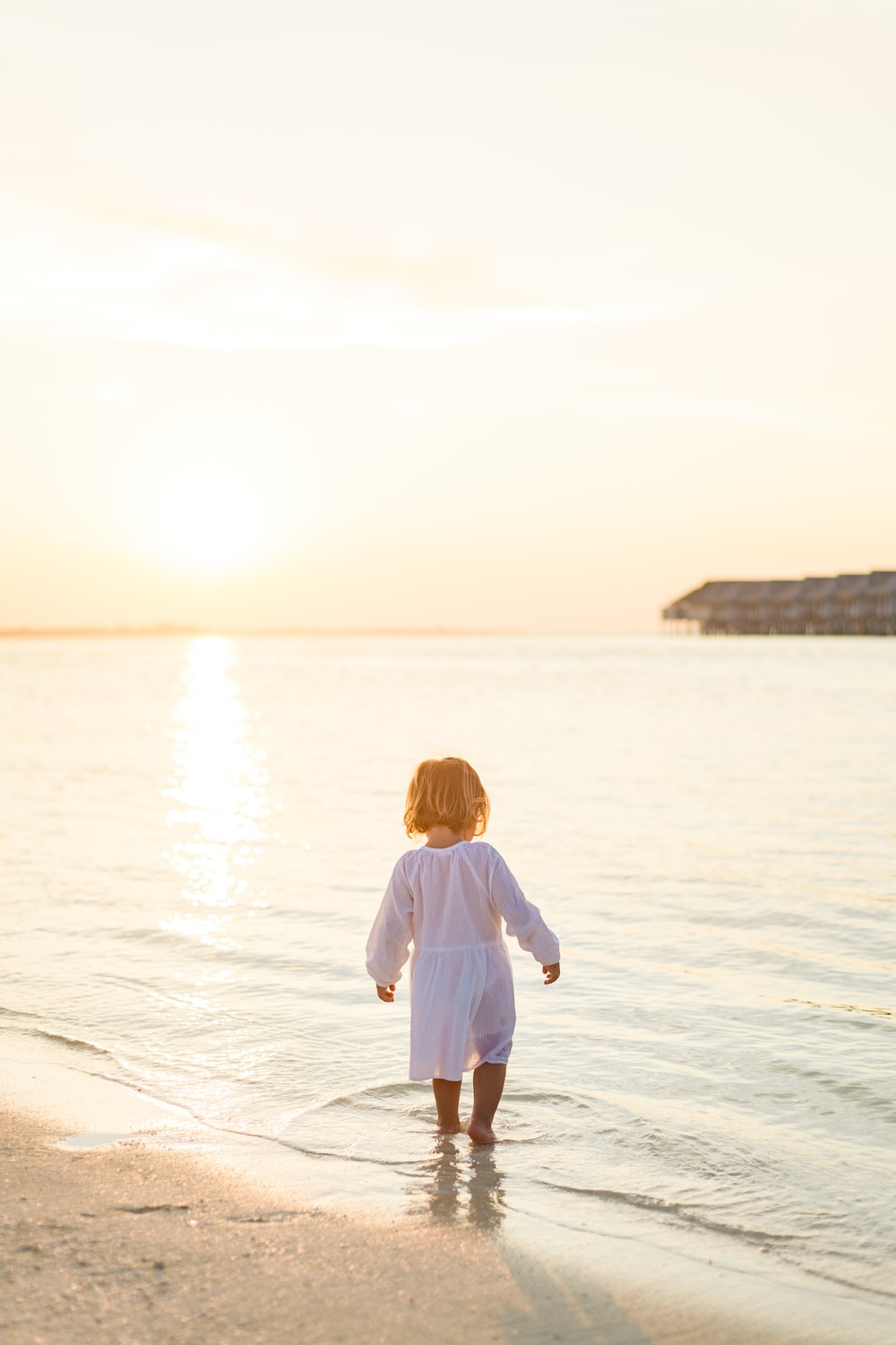 girl in white long sleeve shirt and white pants standing on beach during daytime