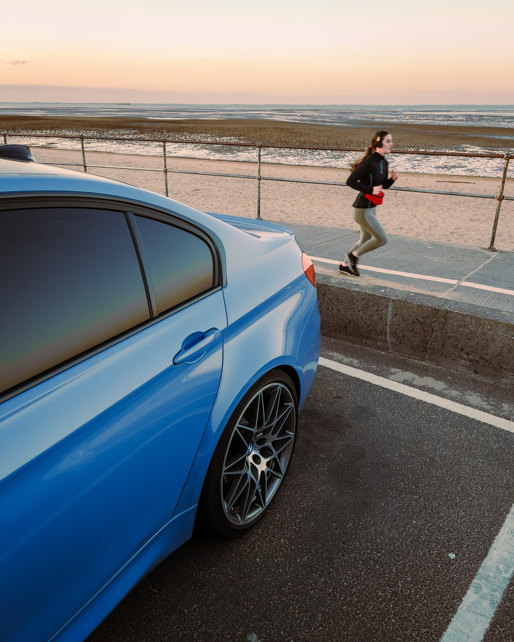 woman in black jacket and black pants standing beside blue car during daytime