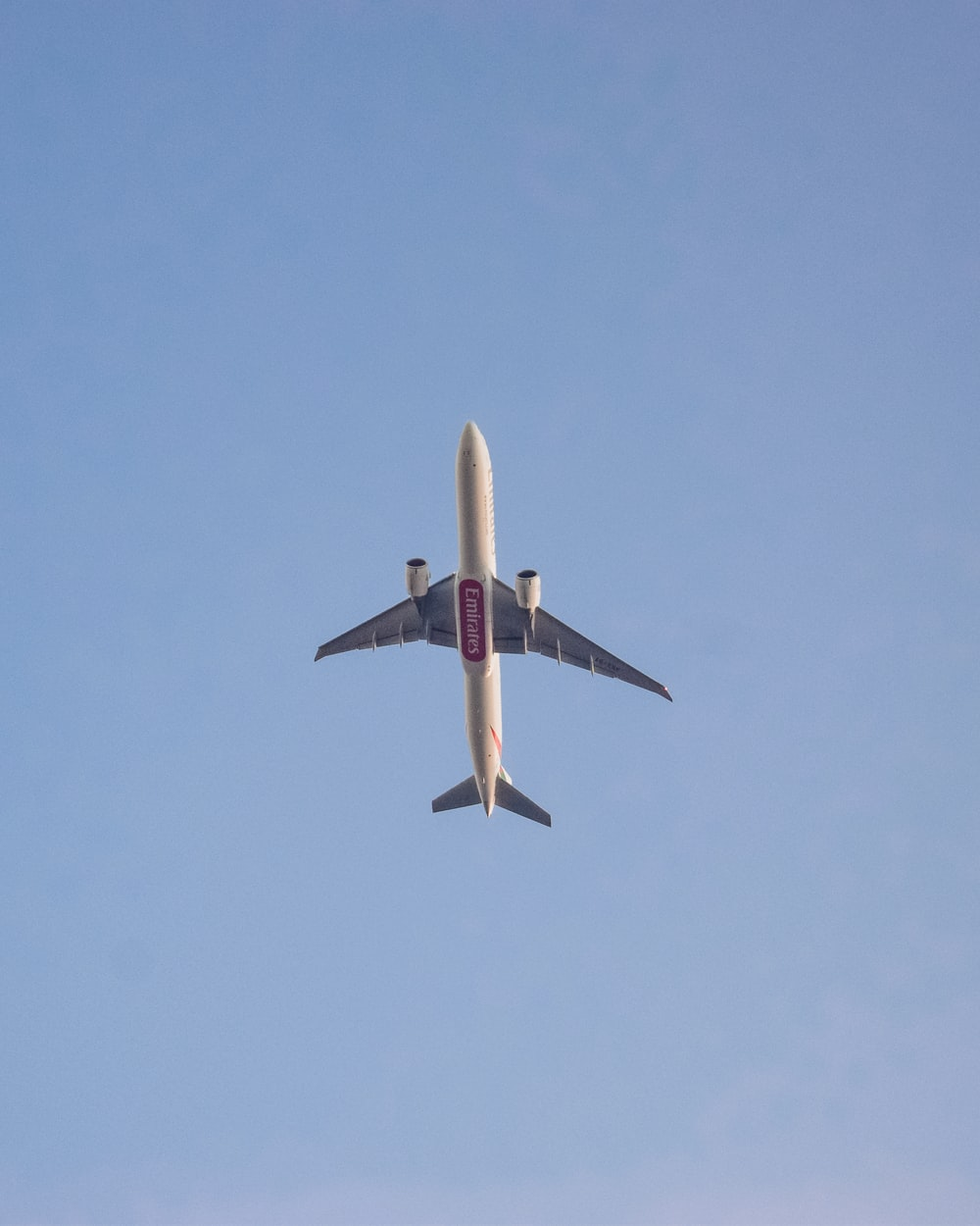 white and red airplane in mid air during daytime