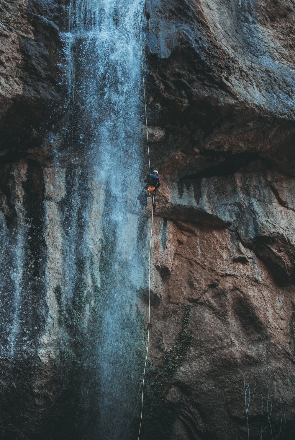 person in blue jacket climbing on rocky mountain during daytime