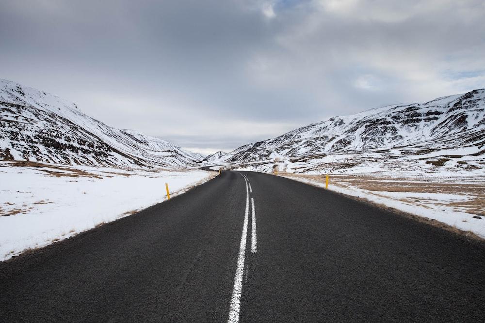 black asphalt road near snow covered mountain under blue sky during daytime