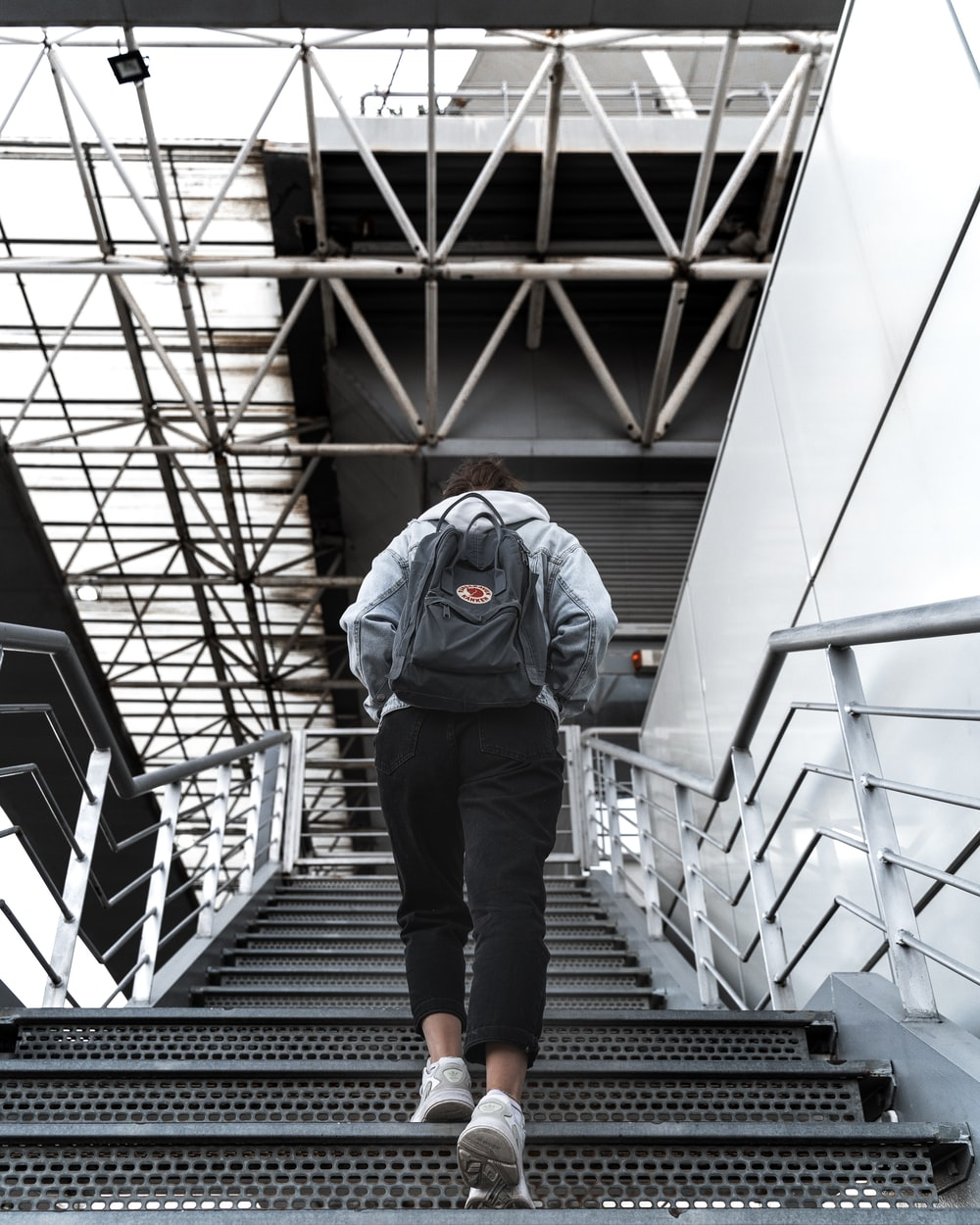 man in blue jacket and black pants walking on black staircase