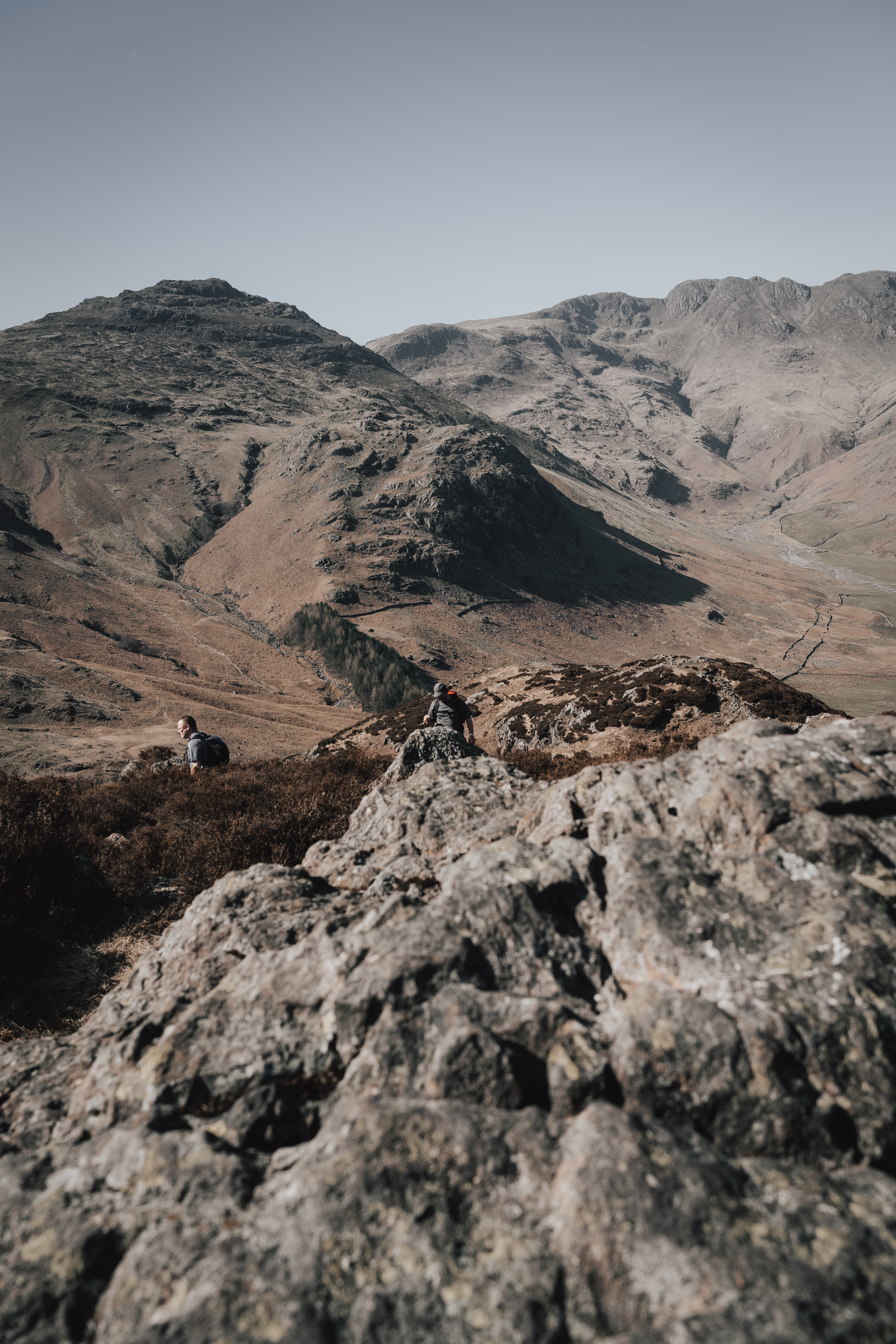 person in black jacket standing on rocky mountain during daytime