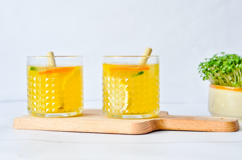 three clear drinking glasses with yellow liquid