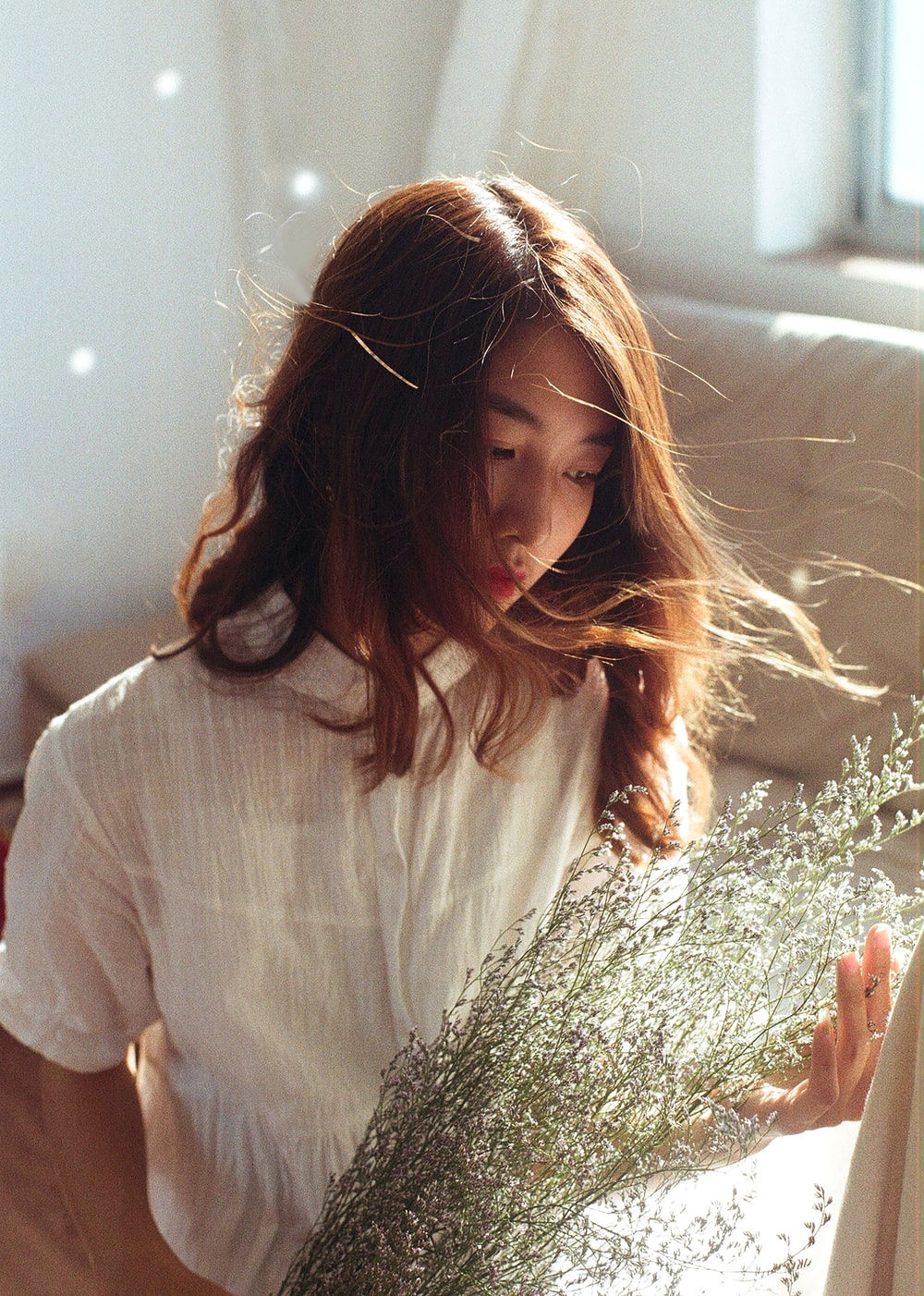 woman in white shirt holding green plant