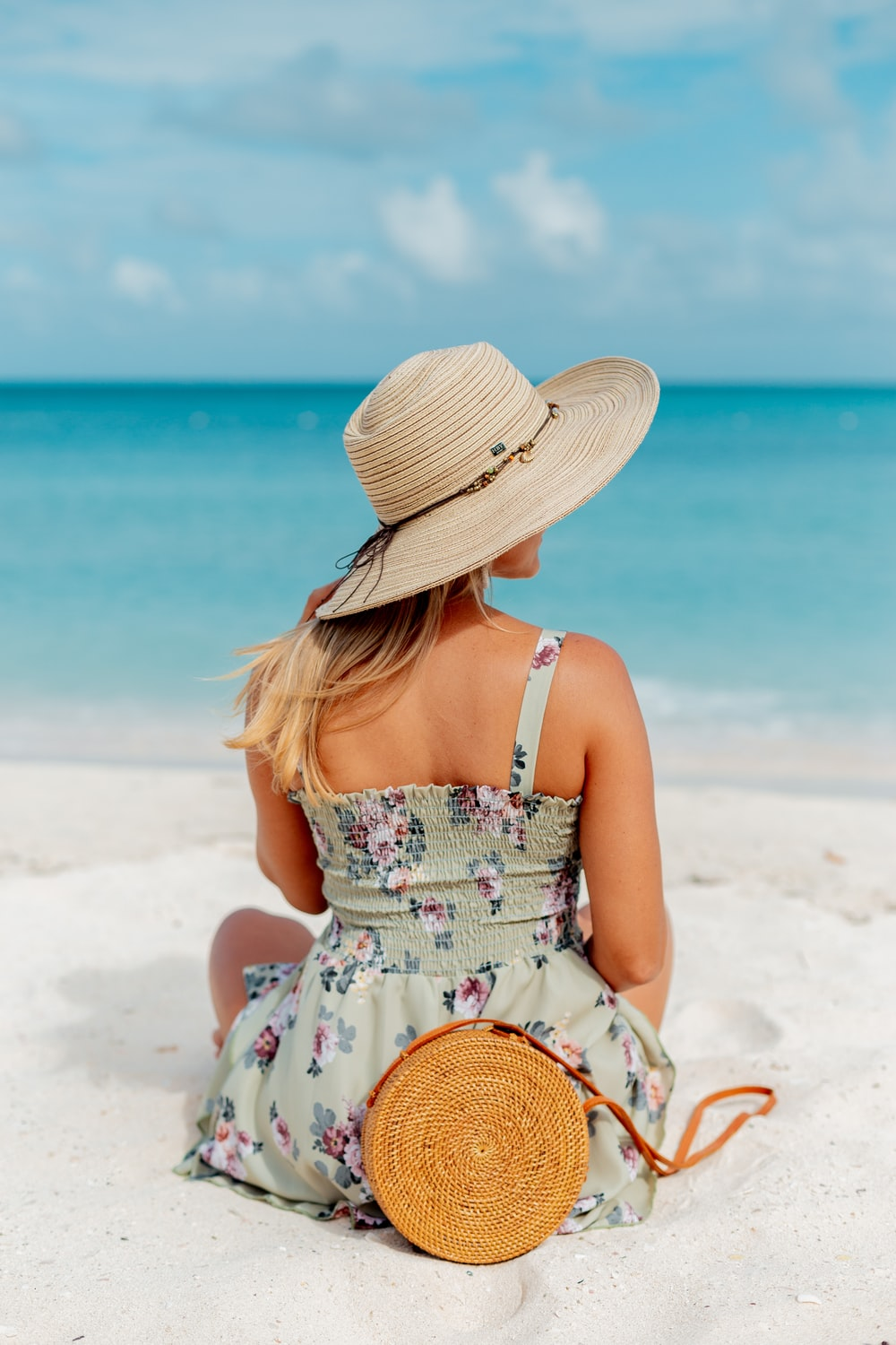 woman in white and pink floral spaghetti strap dress wearing brown sun hat sitting on white