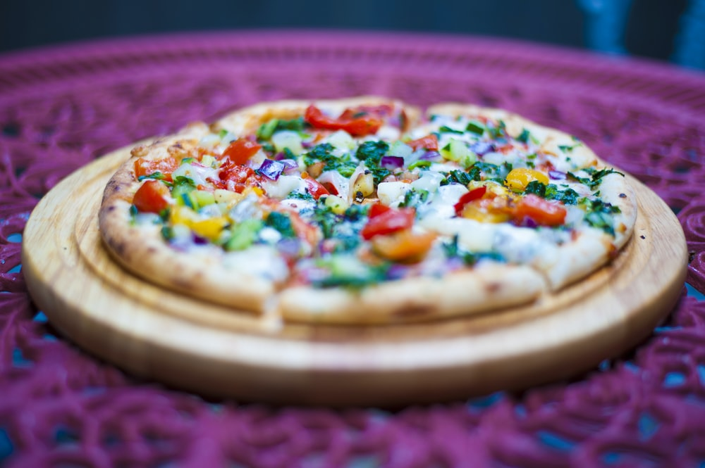 pizza with cheese and green leaves on brown wooden round tray