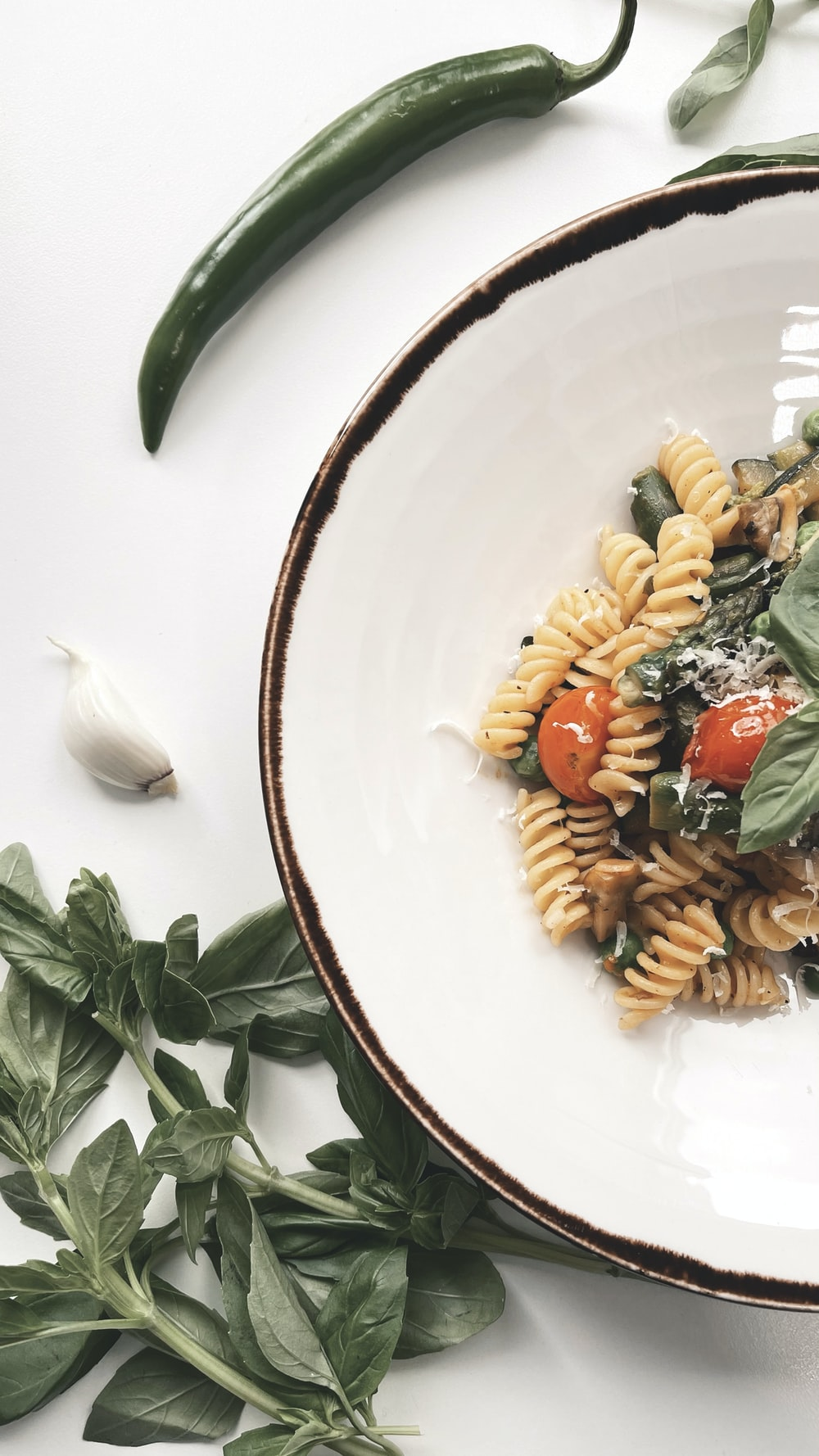 pasta with sliced tomato and green leaf on white ceramic plate