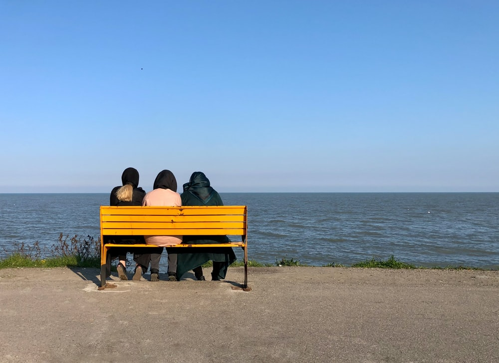 couple sitting on brown wooden bench on beach during daytime