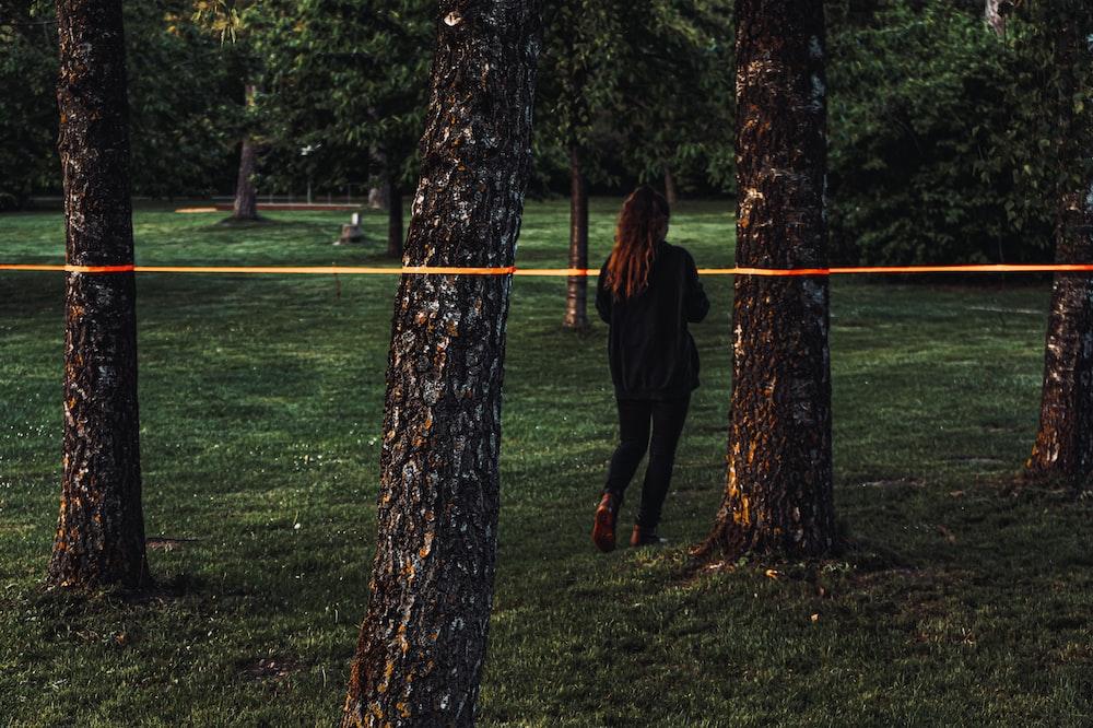 woman in black jacket standing beside brown tree during daytime
