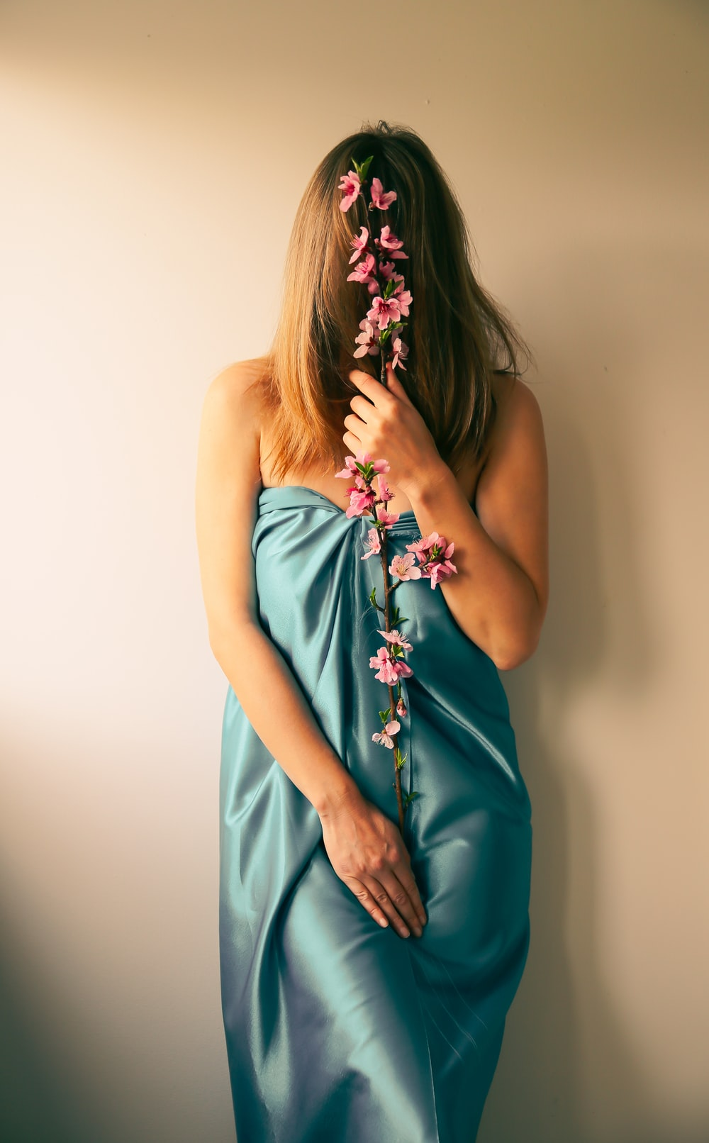 woman in blue sleeveless dress holding bouquet of flowers
