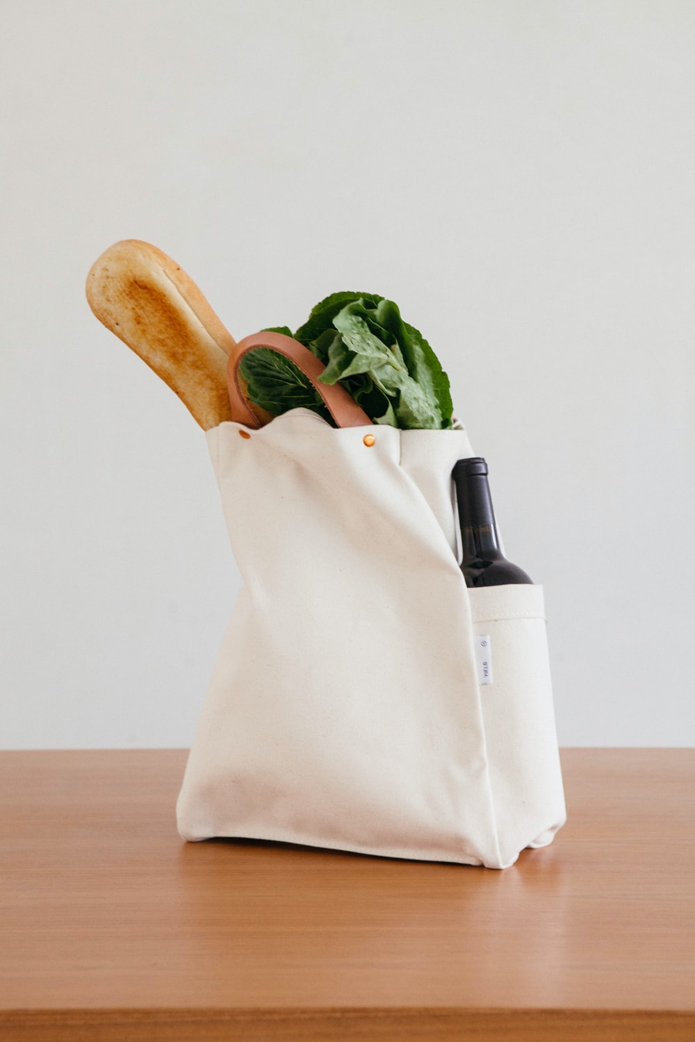 brown wooden rolling pin beside white paper bag
