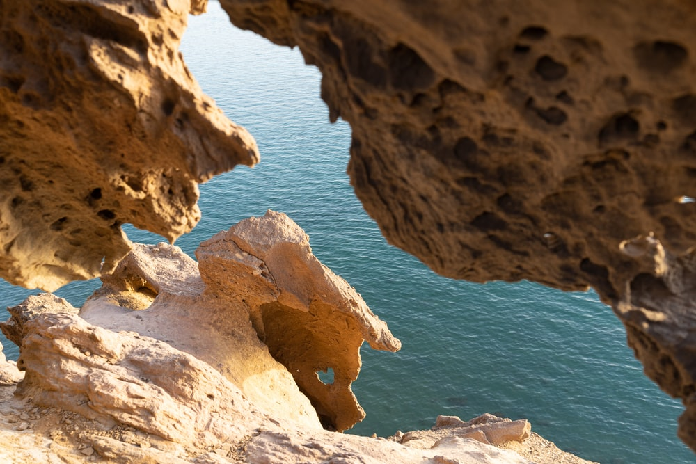 brown rock formation near blue sea during daytime