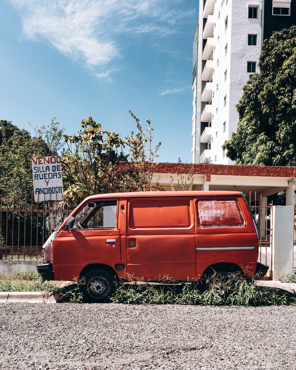 red van parked beside white and brown building during daytime