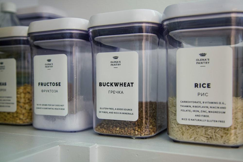 2 clear glass jars on white shelf