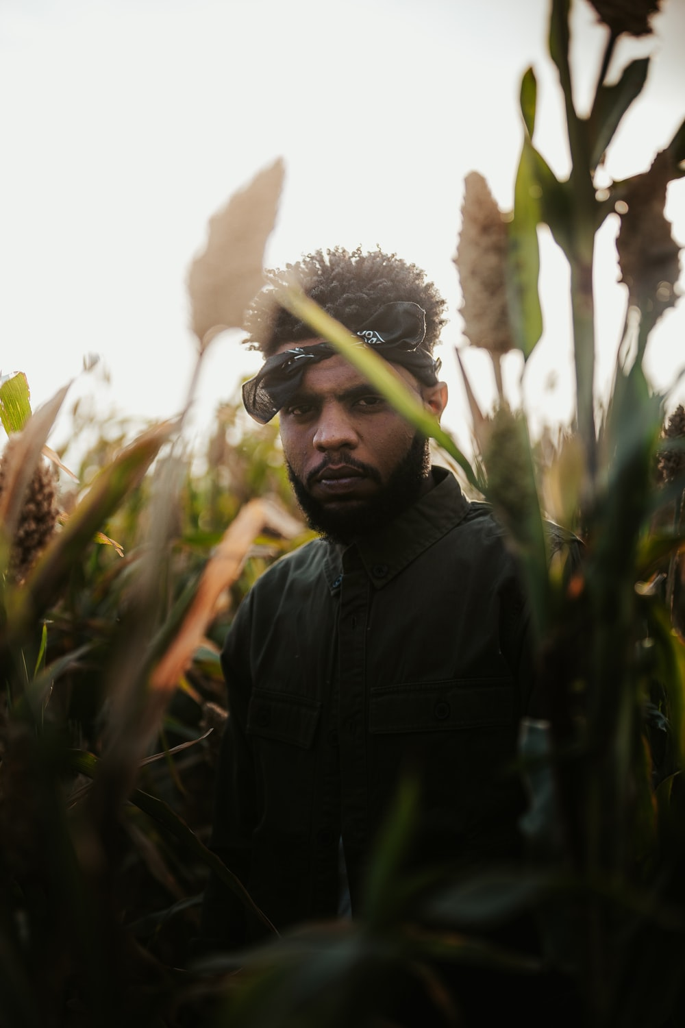 man in black jacket standing in the middle of sunflower field during daytime