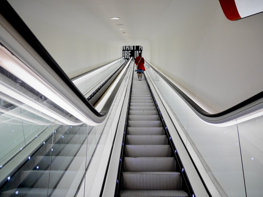 person in red shirt walking on escalator