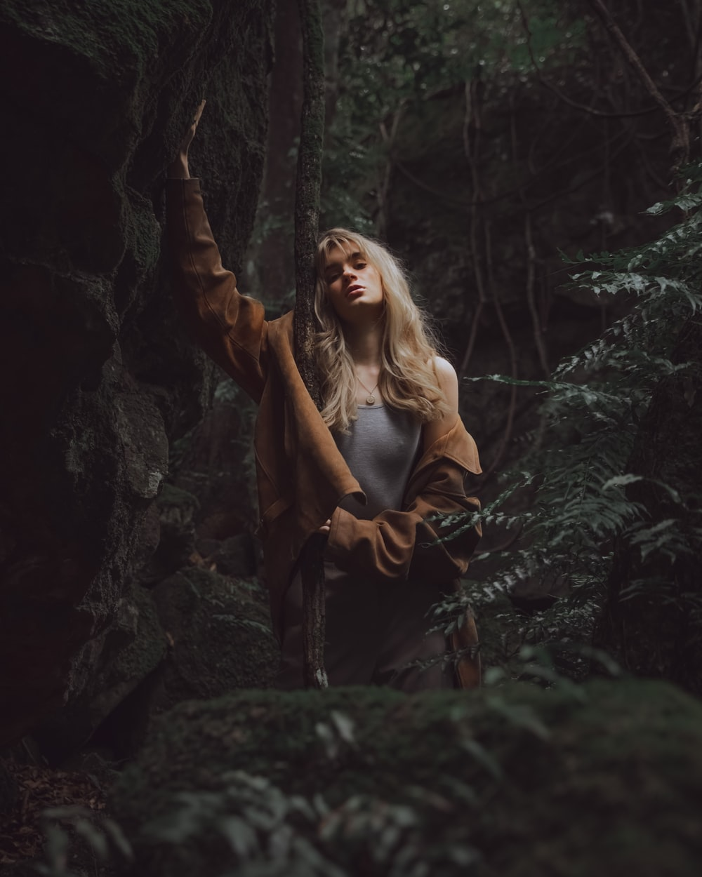 woman in black leather jacket standing in the middle of the woods