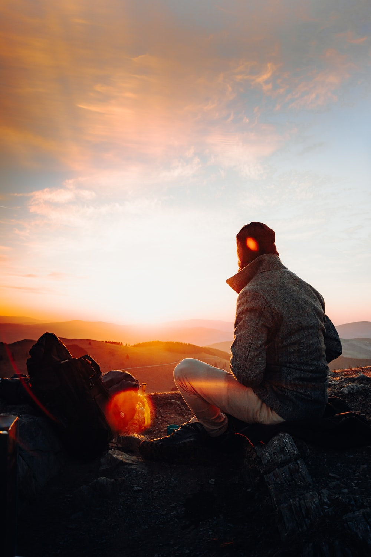 man in gray jacket sitting on rock during sunset