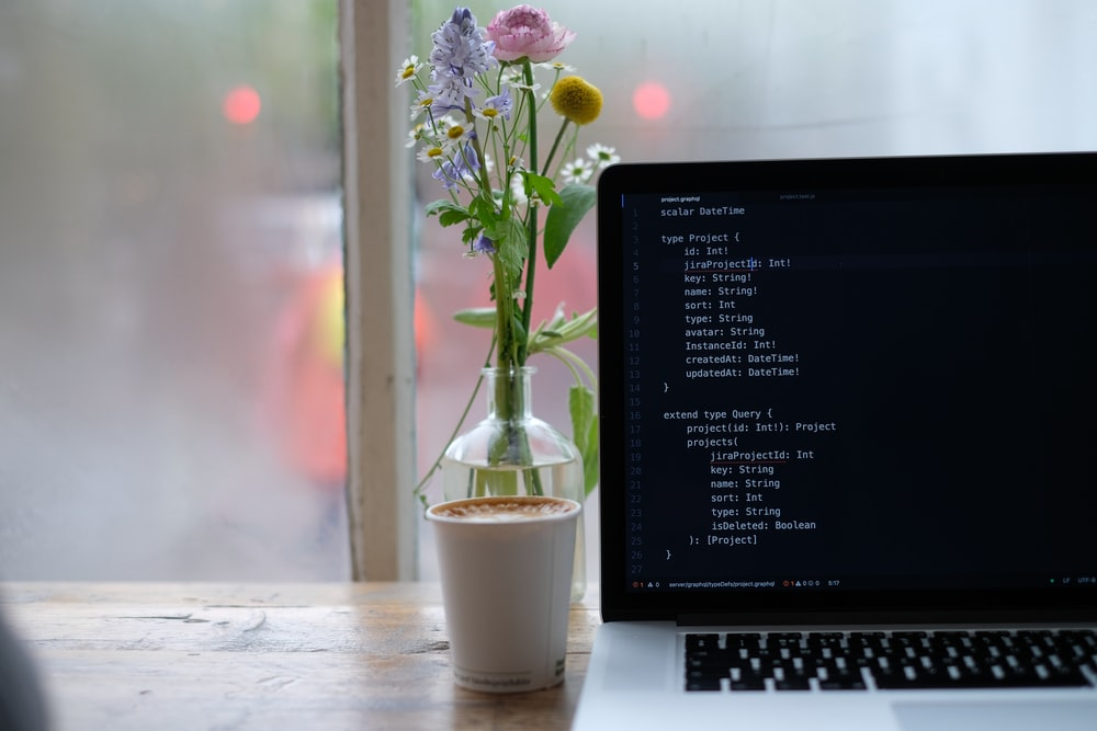 purple flowers in white ceramic vase beside black laptop computer