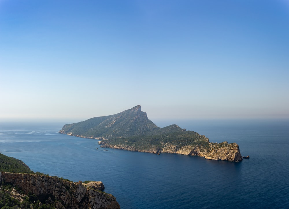 green and brown mountain beside blue sea under blue sky during daytime