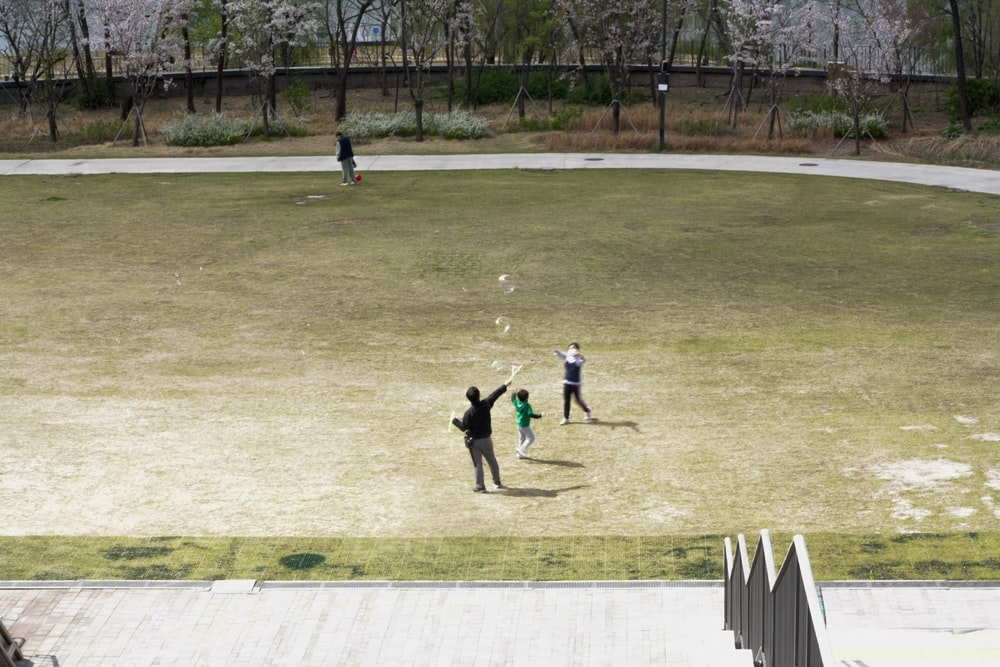 people playing basketball on field during daytime