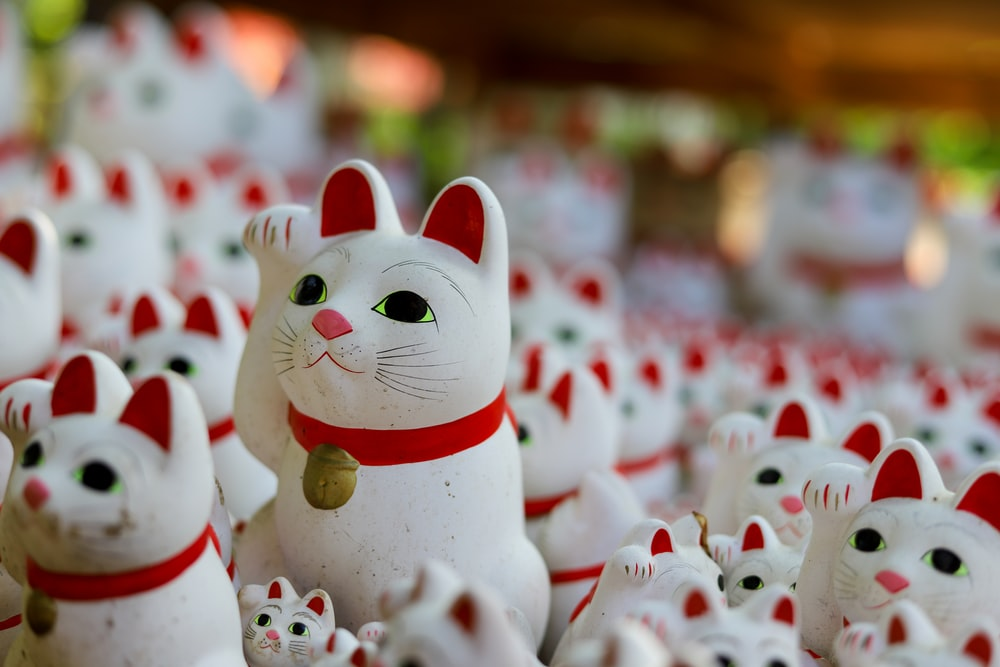 white and red cat ceramic figurines