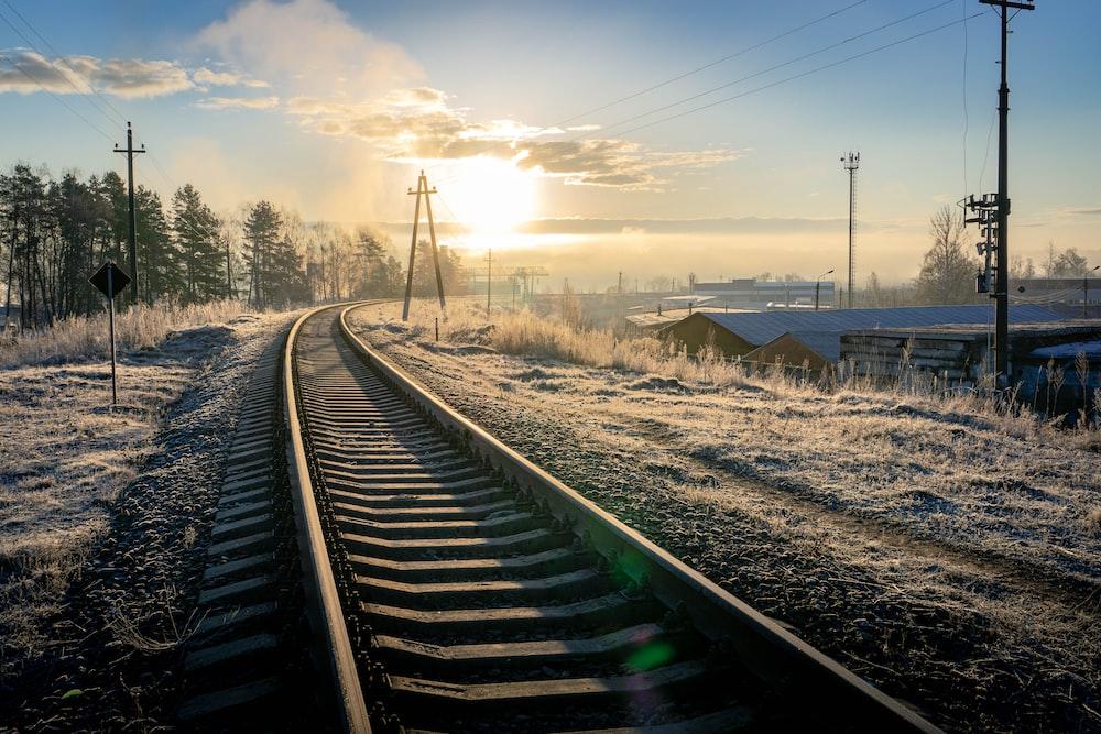 train rail under blue sky during daytime