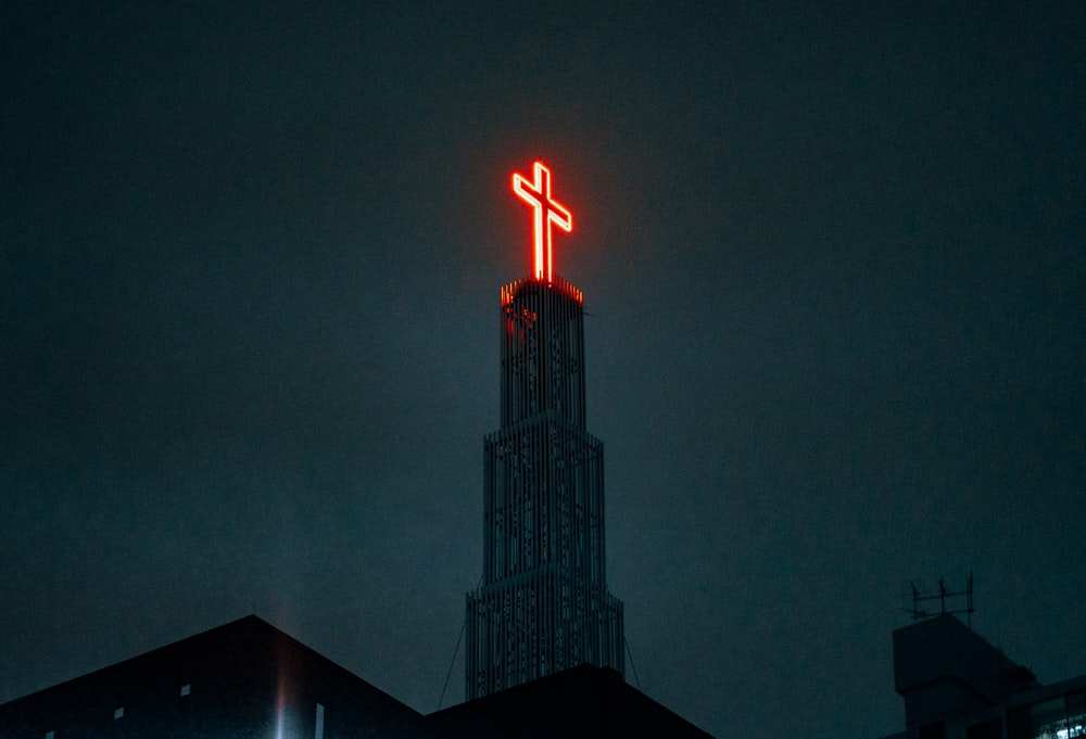 lighted cross on top of building during night time