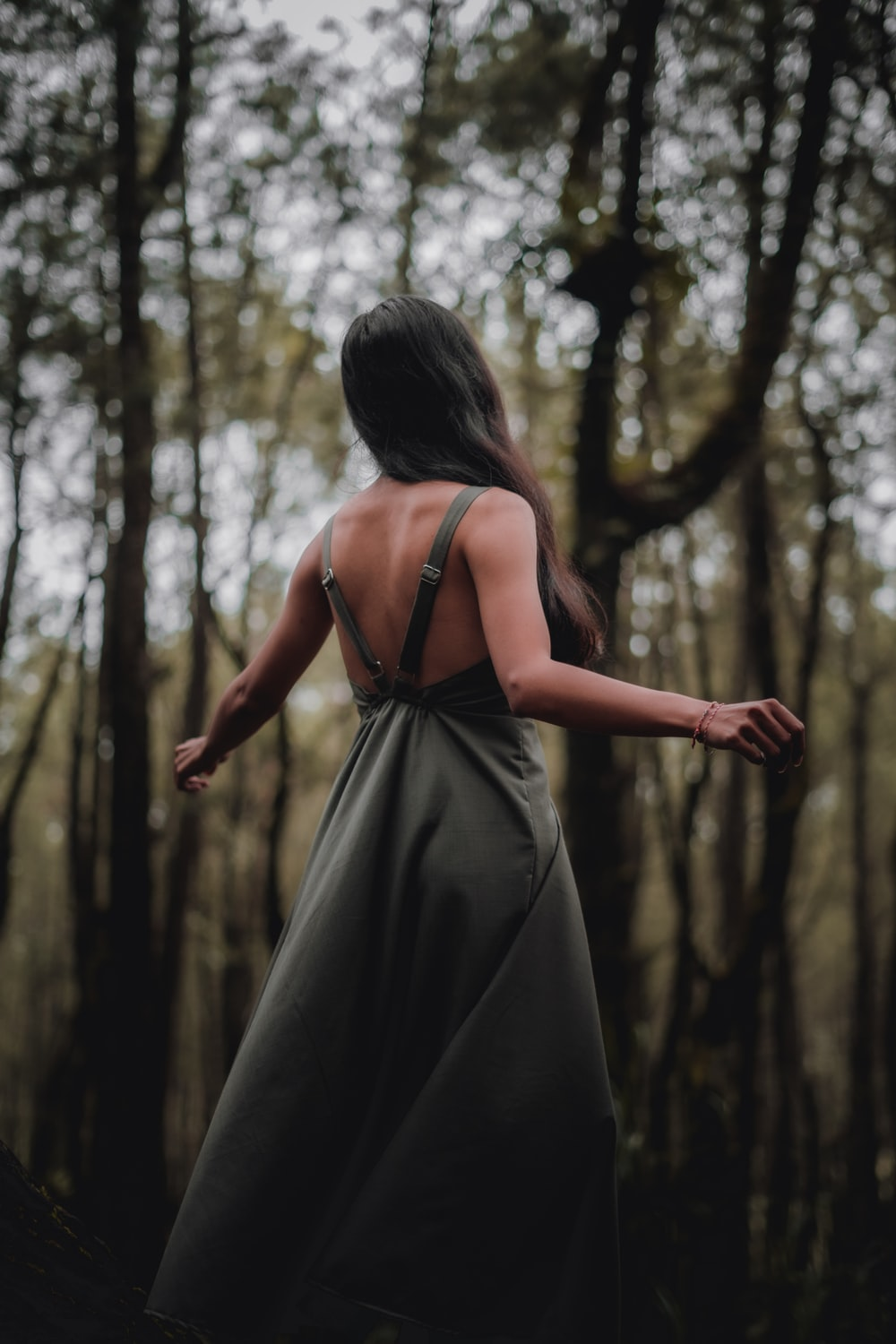 woman in black spaghetti strap dress standing in forest during daytime