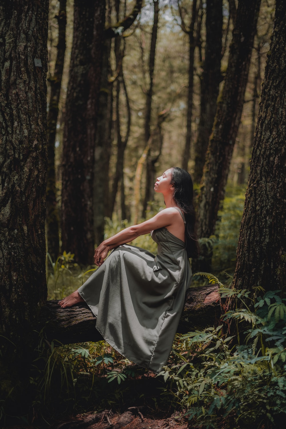 woman in black dress sitting on ground surrounded by trees