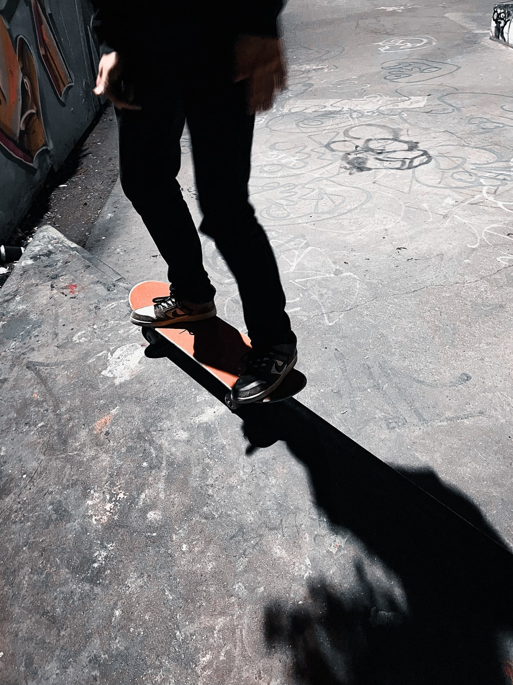 person in black pants and black and orange sneakers standing on gray concrete floor