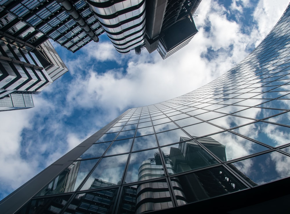 worms eye view of glass building under blue and white sunny cloudy sky during daytime