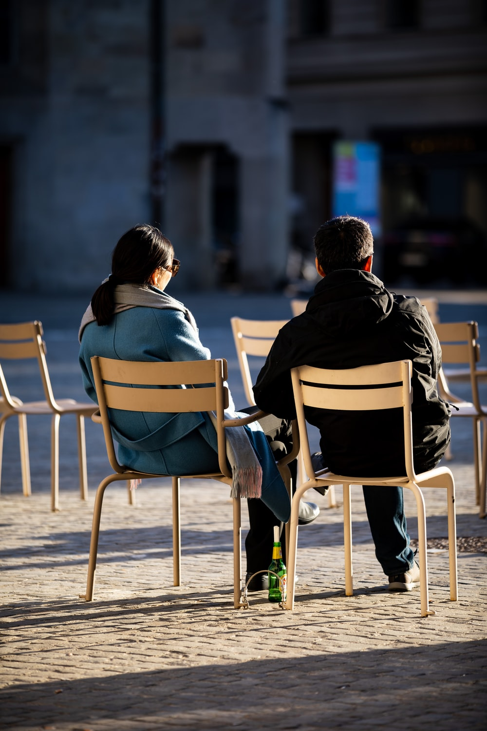 man and woman sitting on white wooden chair during daytime