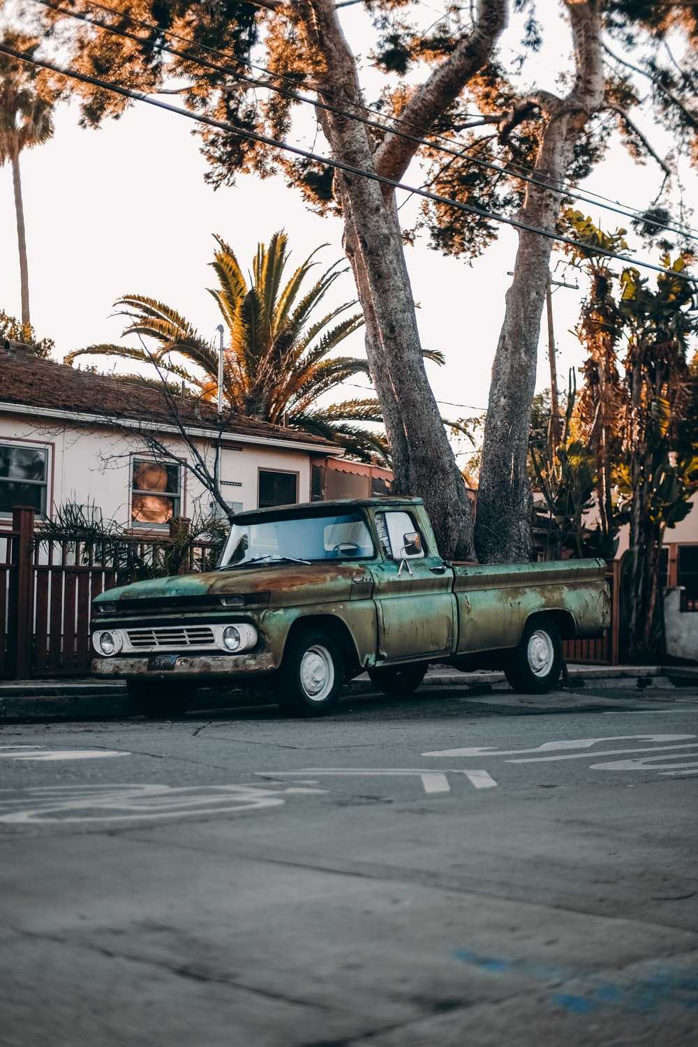 white and brown single cab pickup truck parked near brown wooden house during daytime