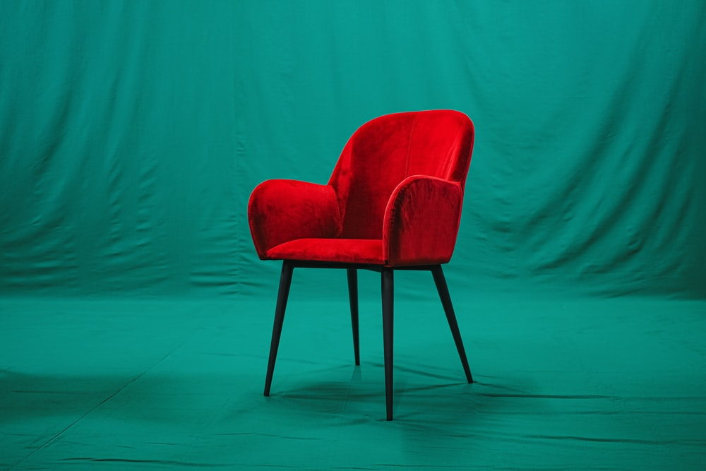 red and black chair beside green wall