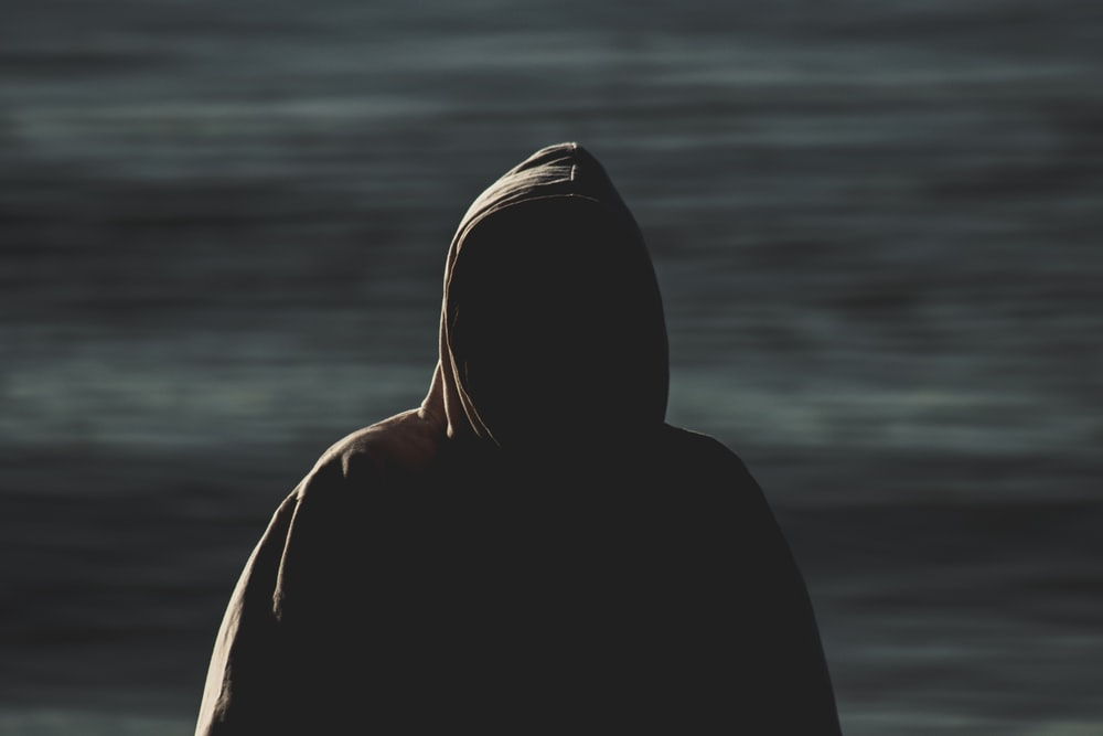 person in black hoodie standing near body of water during daytime