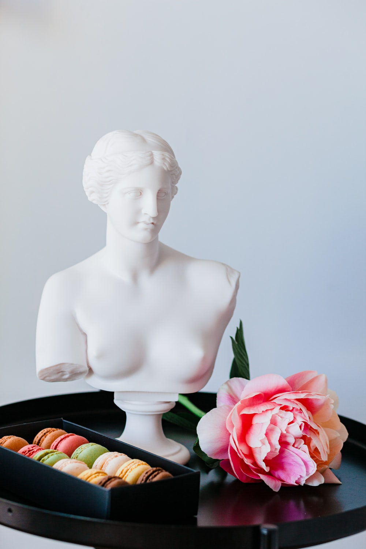 white ceramic woman figurine beside red rose