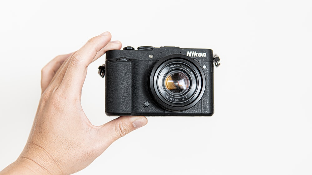 person holding black camera on white background