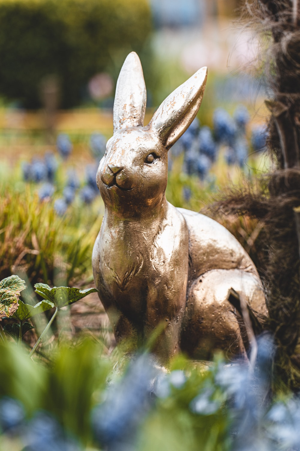 brown rabbit statue on green grass during daytime