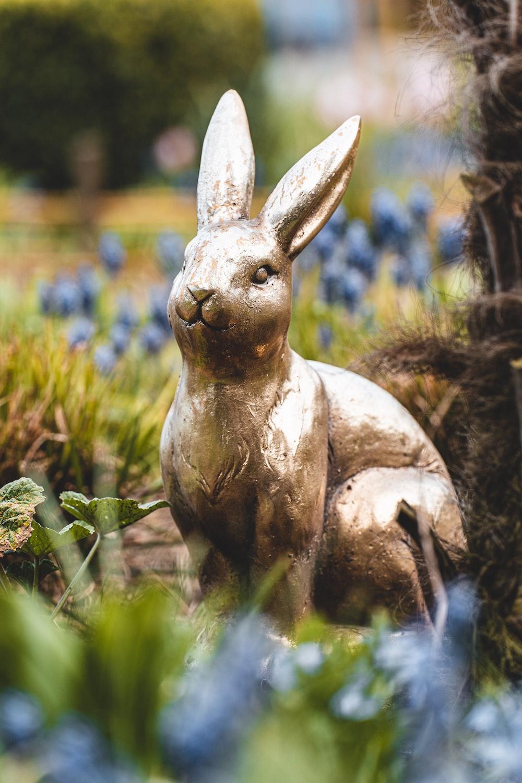 brown rabbit statue on green grass during daytime