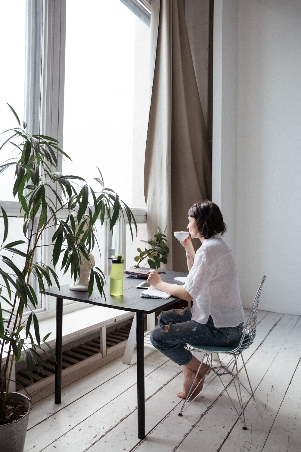 woman in white shirt sitting on chair in front of computer