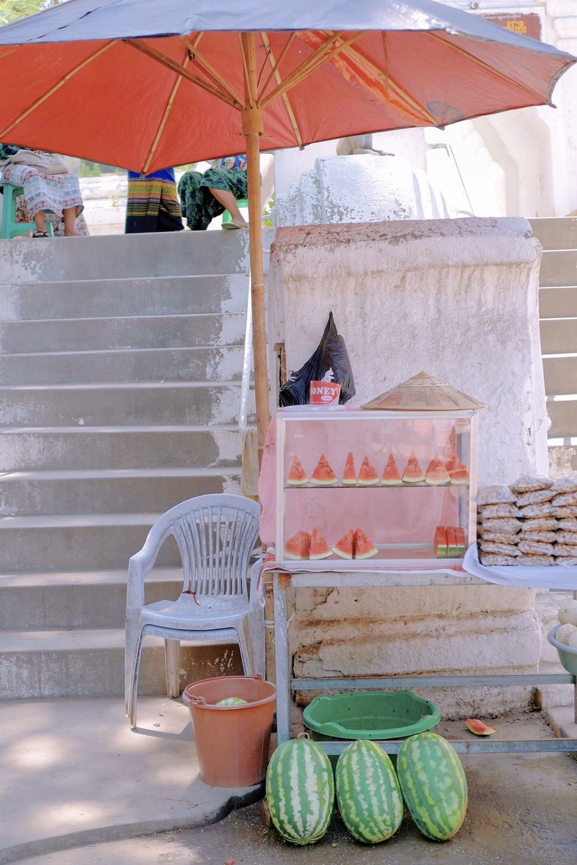 white plastic armchair beside white concrete wall